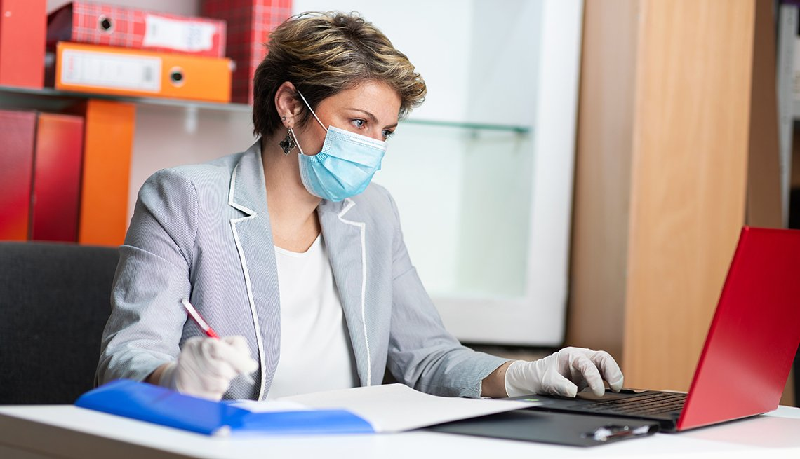 woman at work using a laptop in her office while wearing a facemask
