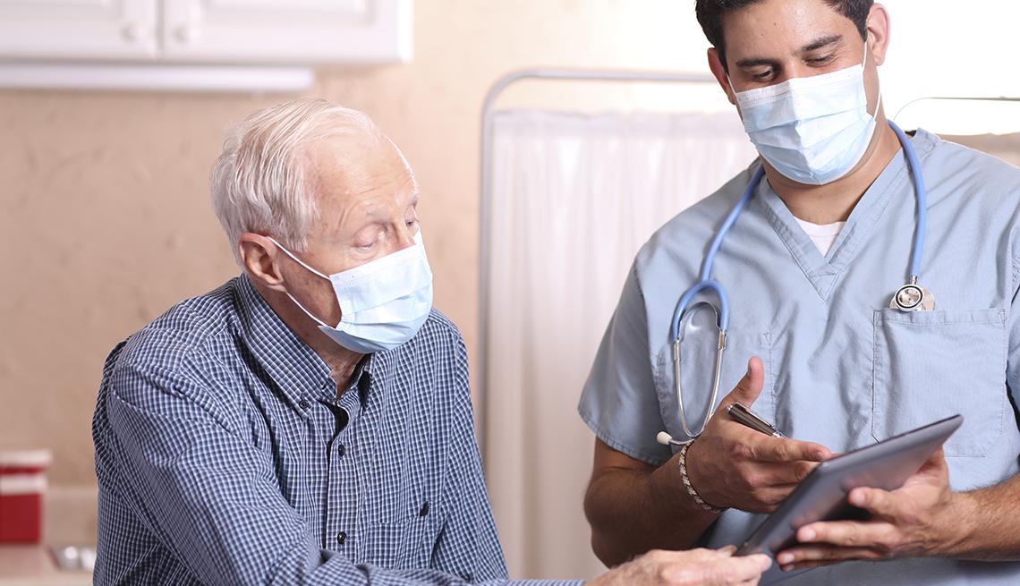 Un hombre conversa con su doctor, ambos usan mascarilla