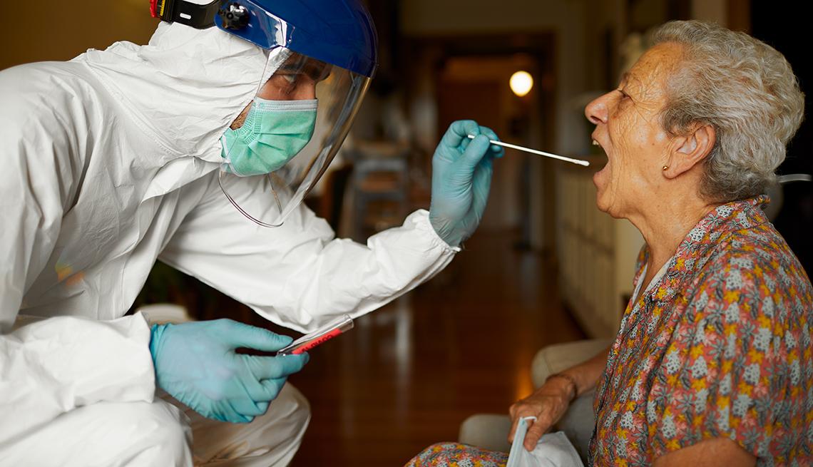 Un empleado con equipo de protección le hace la prueba de coronavirus a una persona mayor
