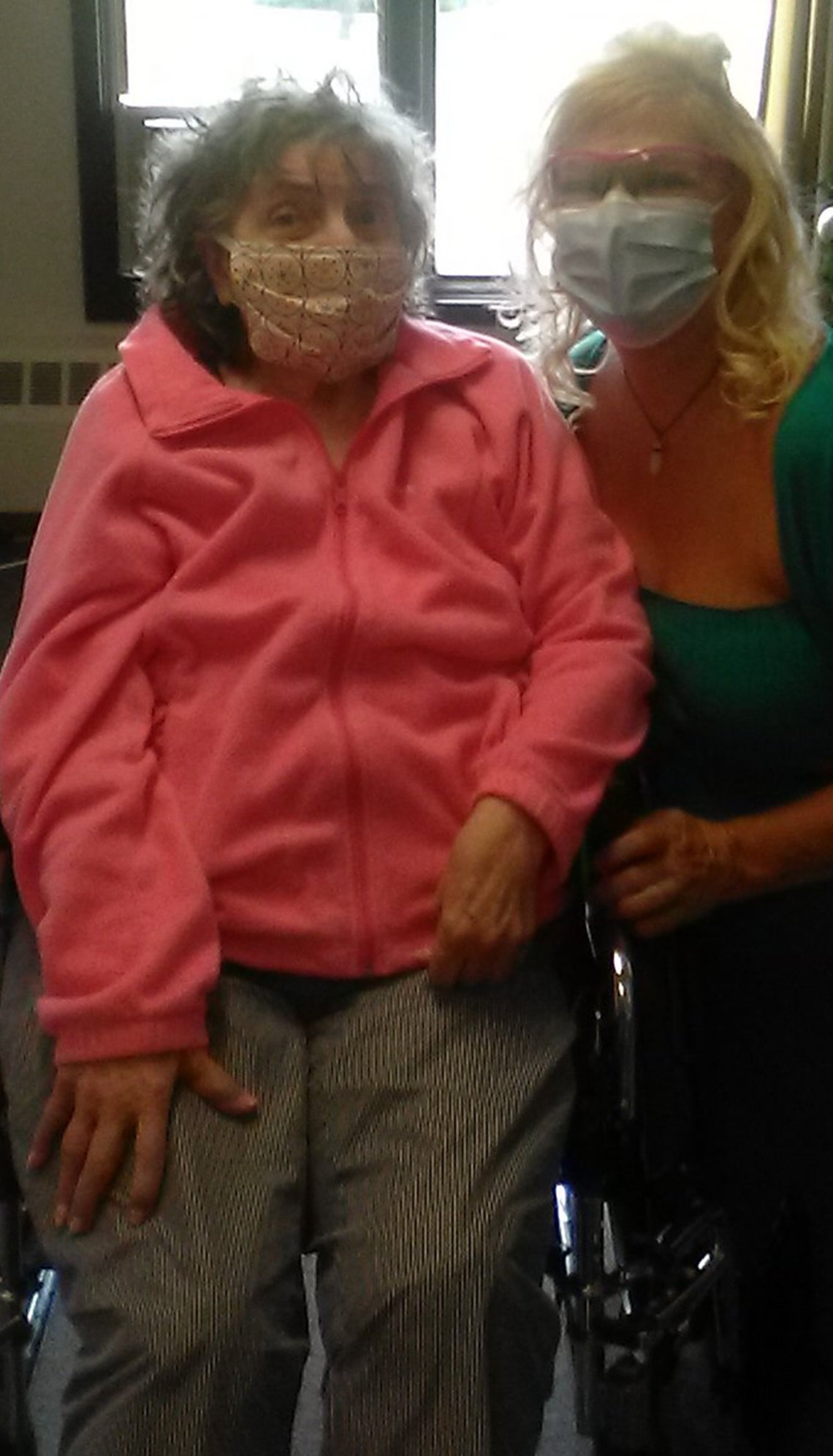 Woman and her mother who is seated in a wheelchair. Both are wearing face masks.