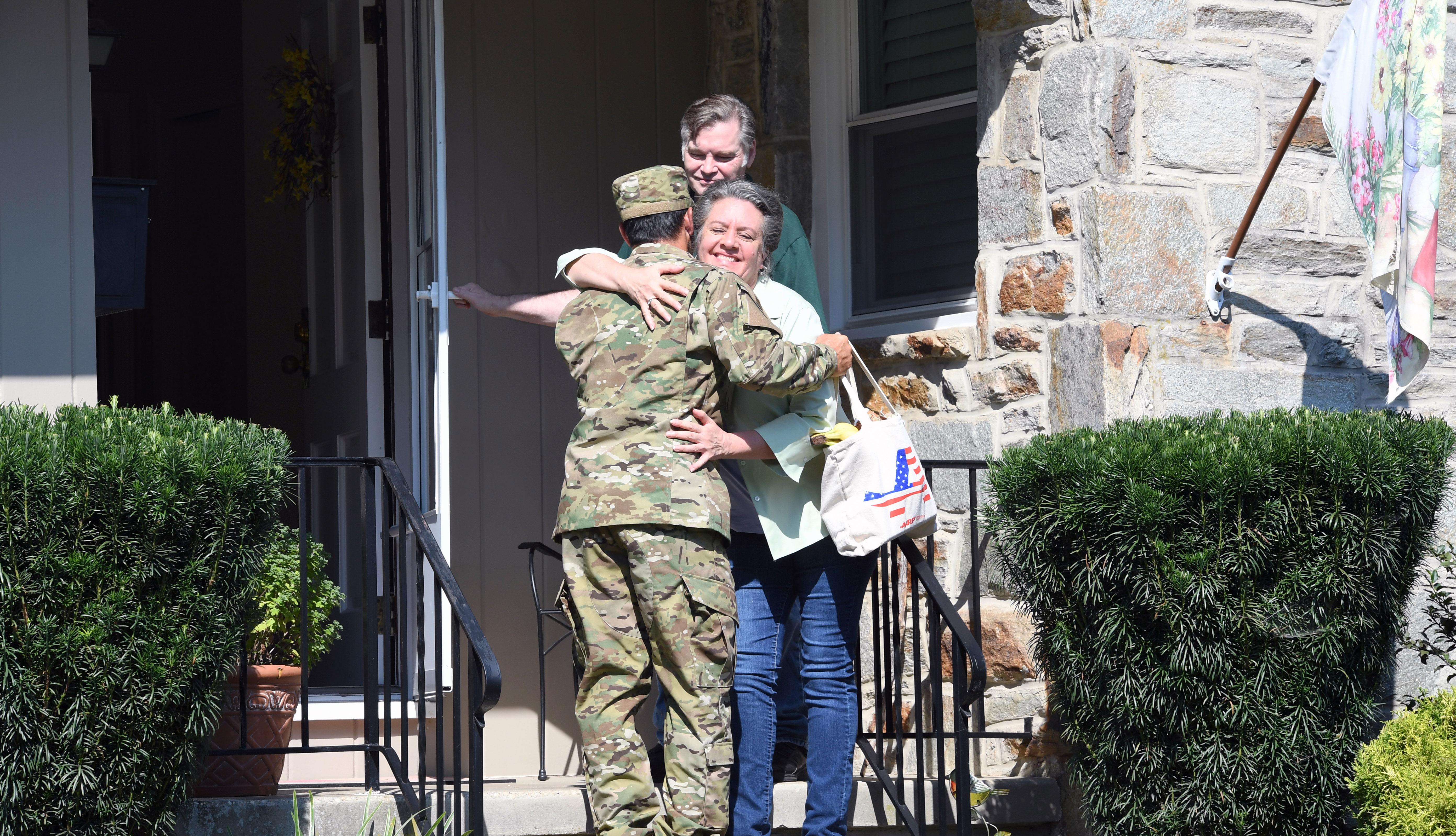 Una madre abraza a su hijo vestido de militar