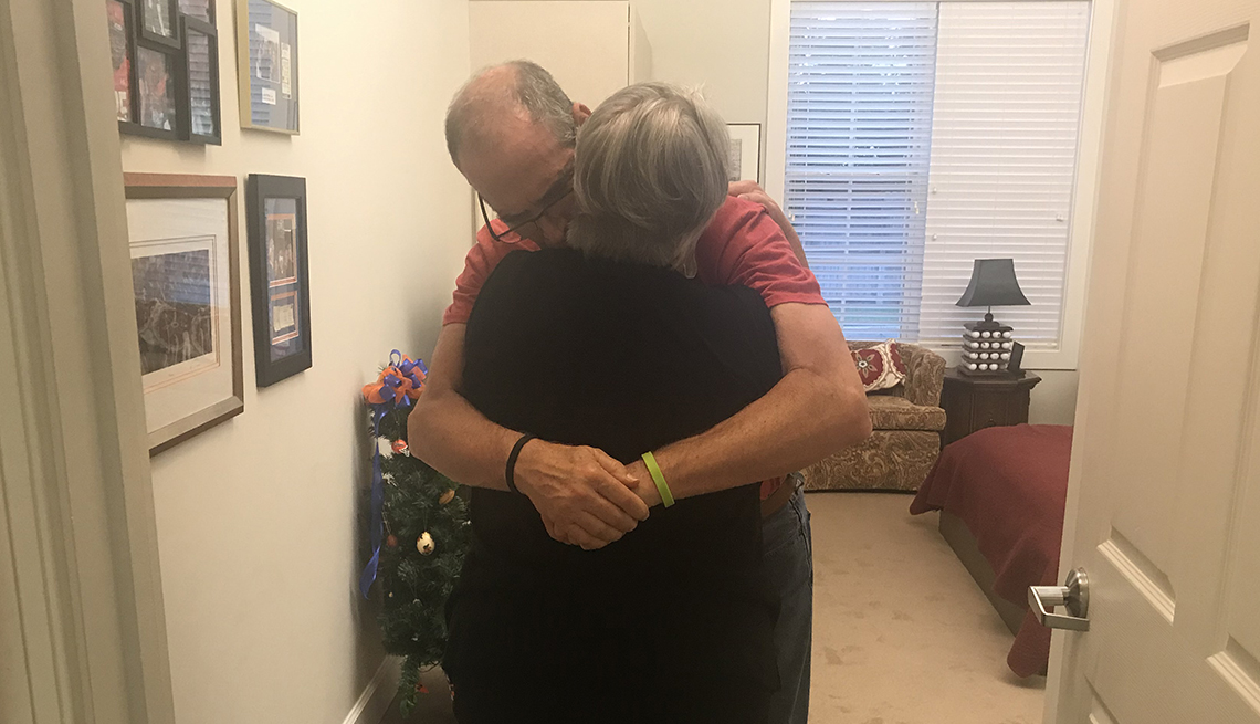 Husband and wife hugging at his nursing home.