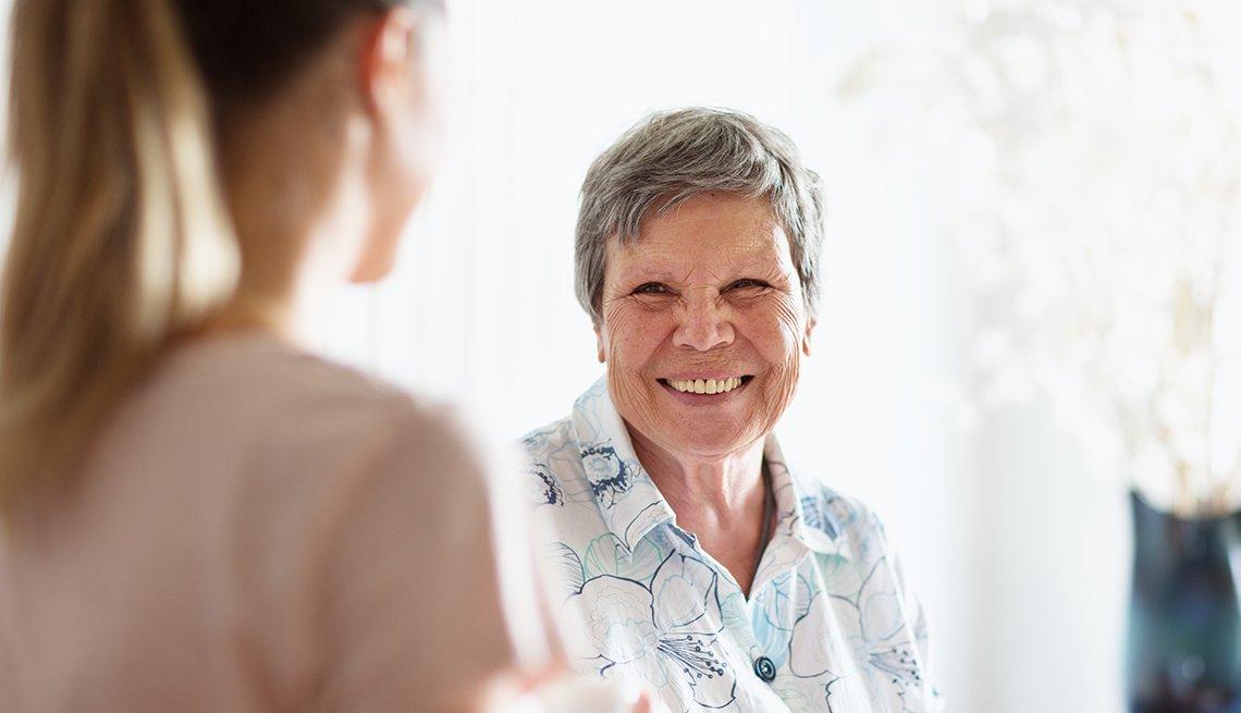 Una cuidadora ayuda a una mujer mayor