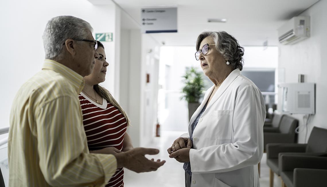 un médico en un hospital hablando con un hombre y una mujer