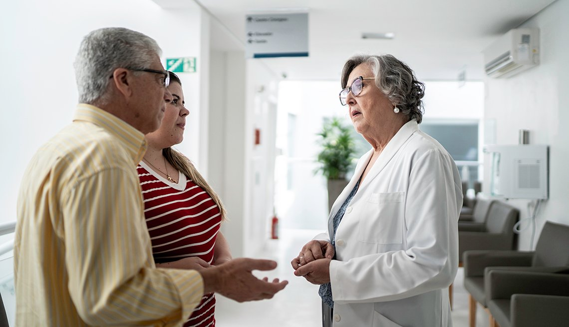 doctor in a hospital talking to a man and his daughter