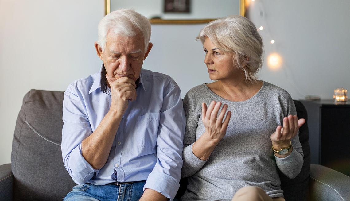 Una pareja casada sentada en el sofá teniendo un desacuerdo