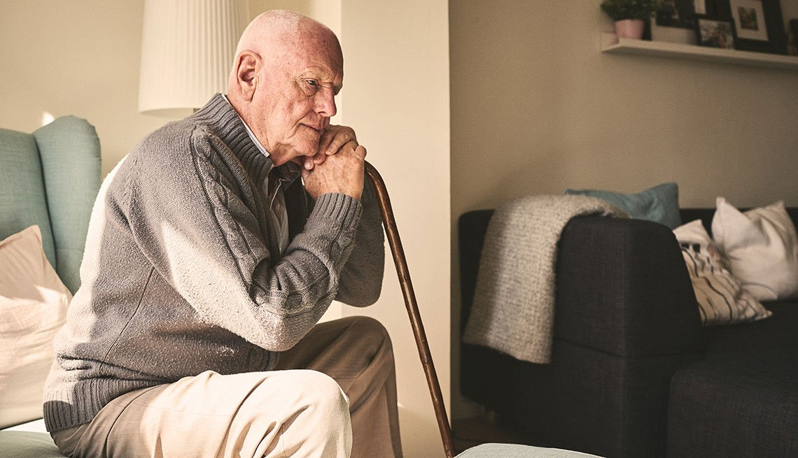 Man sitting alone holding a cane looking sad
