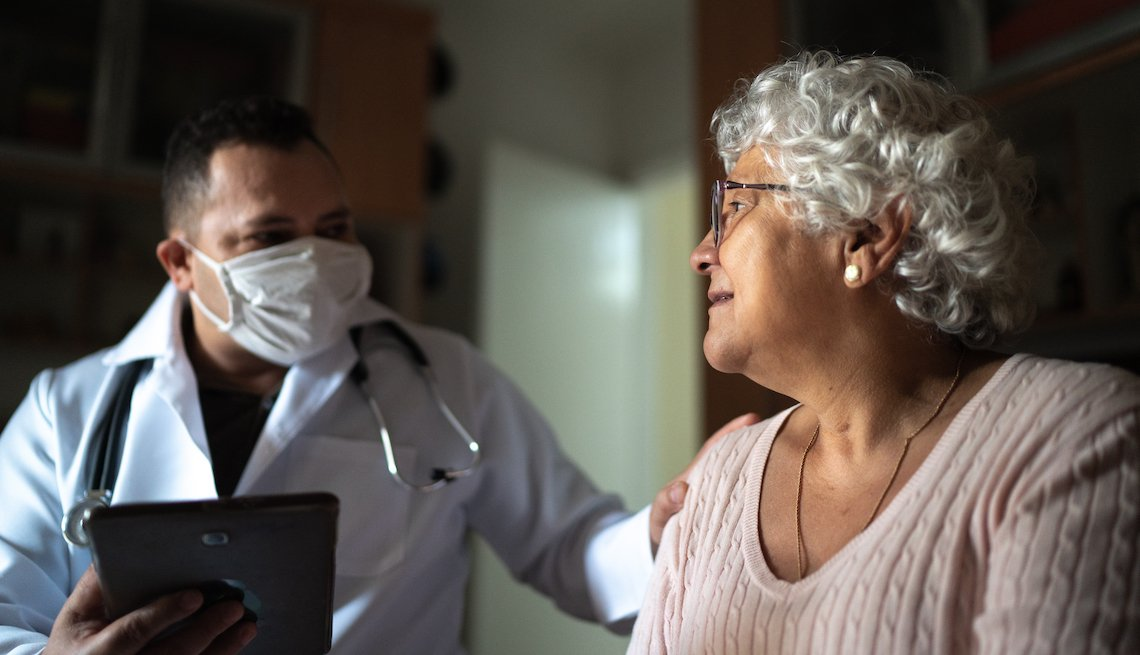 Hispanic health care worker and a senior woman during a nursing home visit