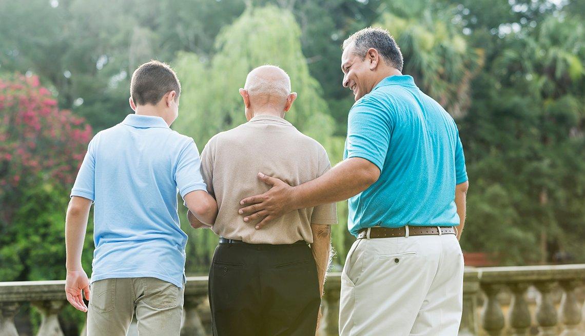 Padre e hijo ayudan al abuelo a caminar