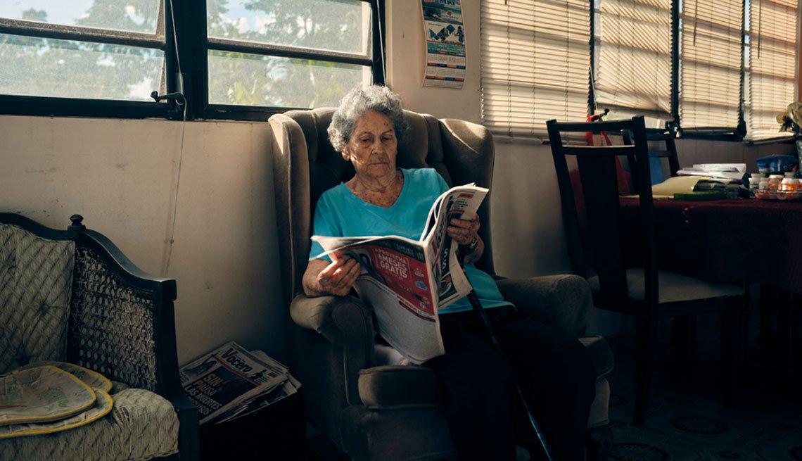 Encarnita Munich lee un periódico en la sala de su hogar