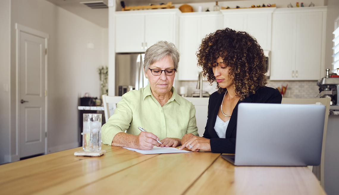 A woman filling out paperwork with a family member.
