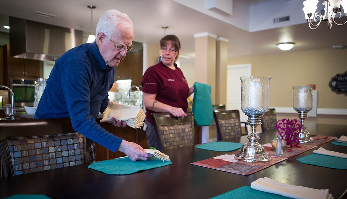 Resident and staff member at the Green House Homes in Colorado setting the table for dinner.