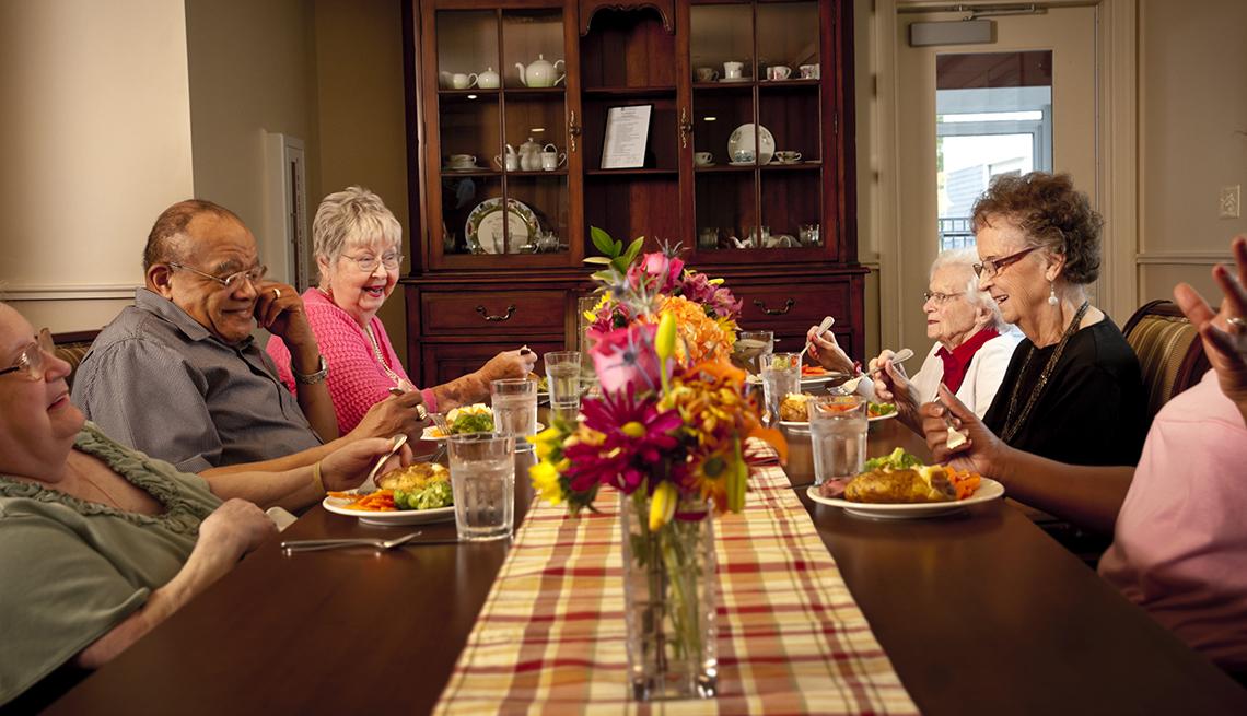 Residents of a household model nursing home eating dinner together
