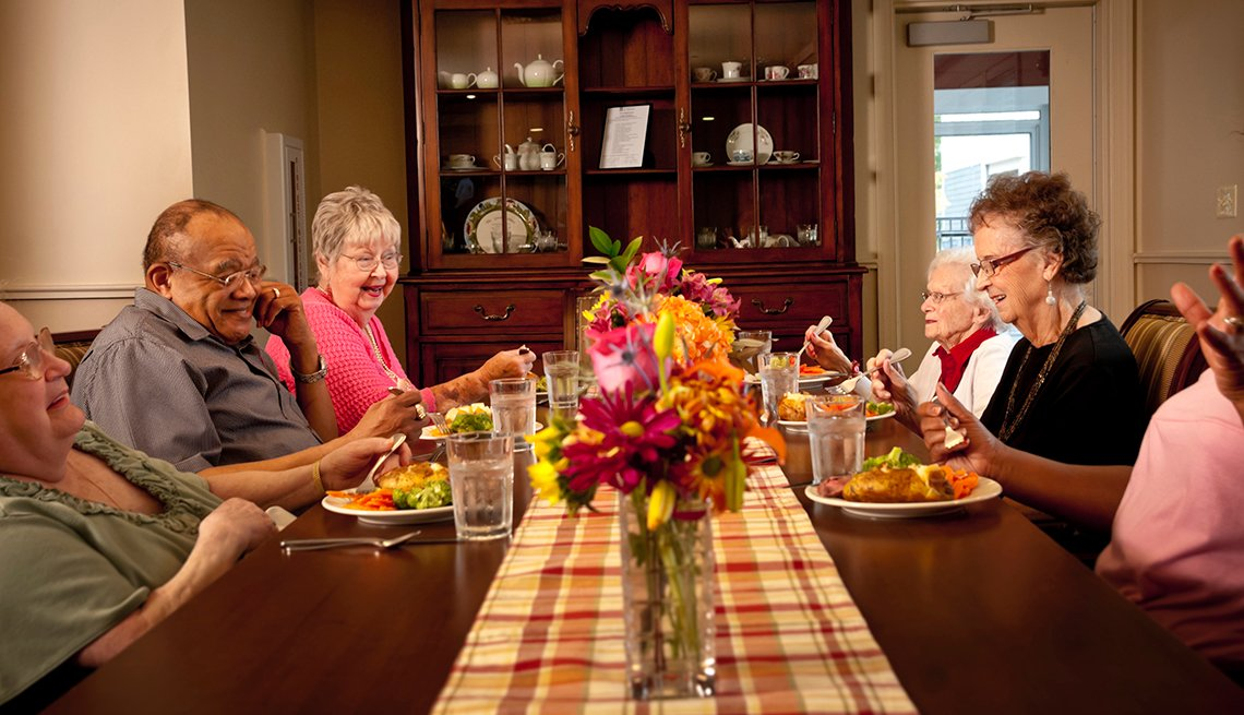 Residents of a household model nursing home eating dinner together