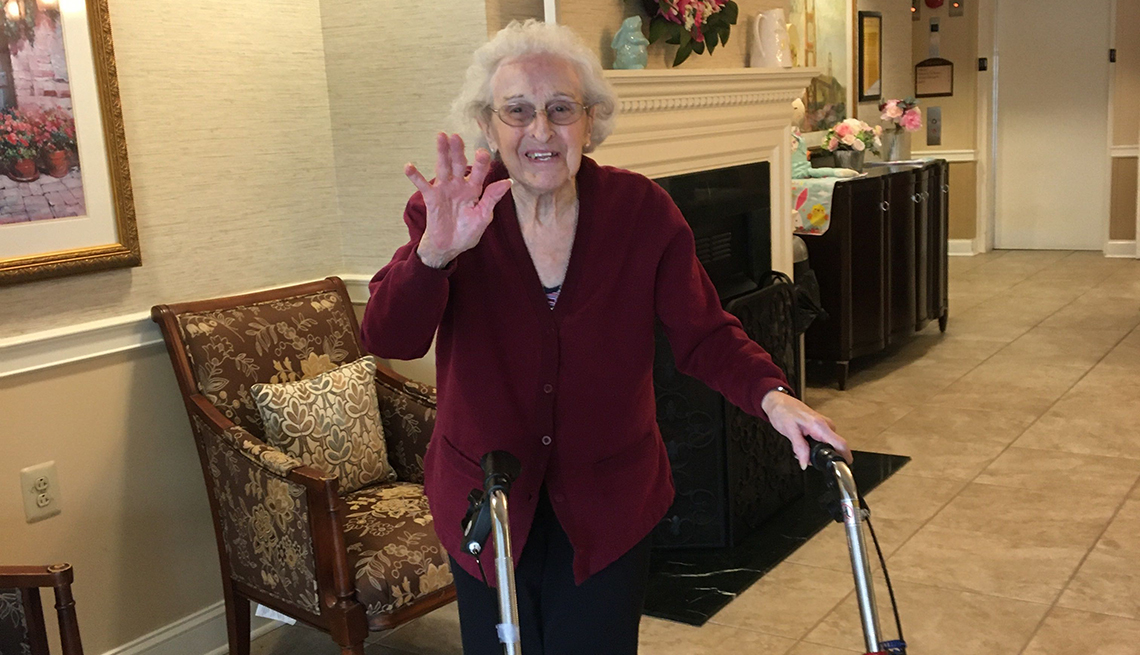 Ida smiling and waiving inside her assisted living home