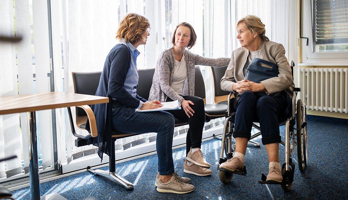 Una doctora conversa con una mujer en silla de ruedas y su hija adulta