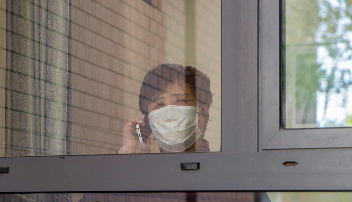 Woman wearing a face mask holding a telephone and looking out a nursing home window