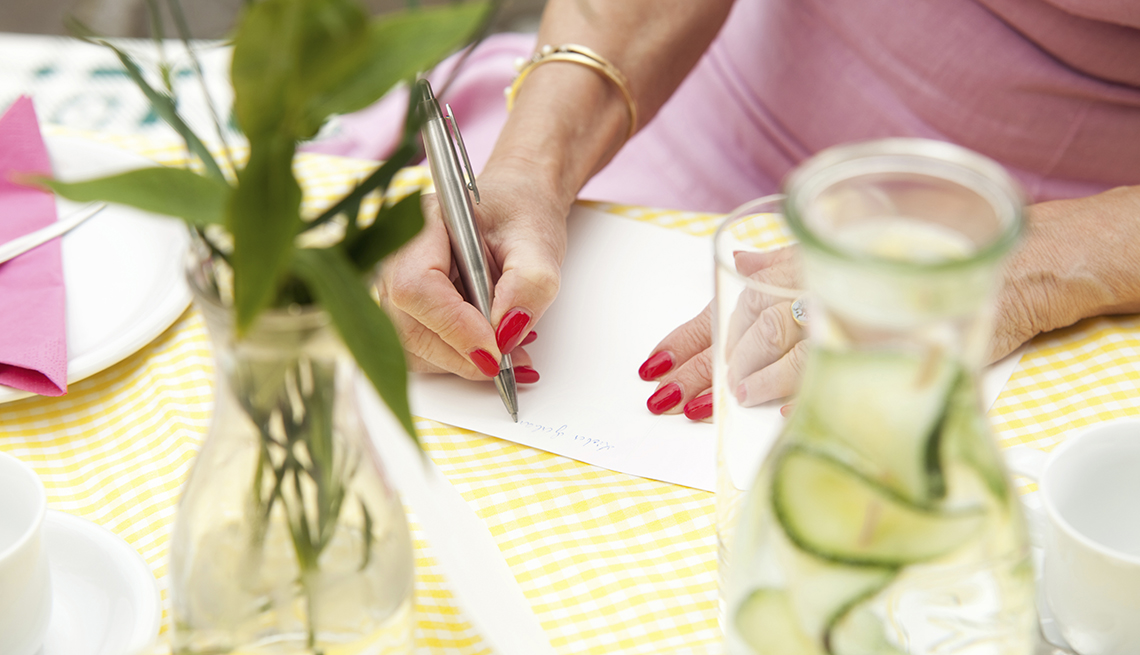 the hands of a woman sitting at a table writing in a sympathy card