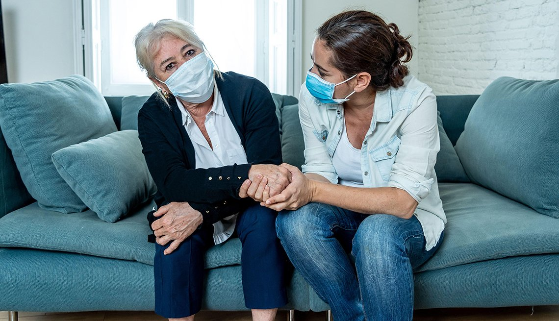 A woman and her mother on the couch both wearing face masks