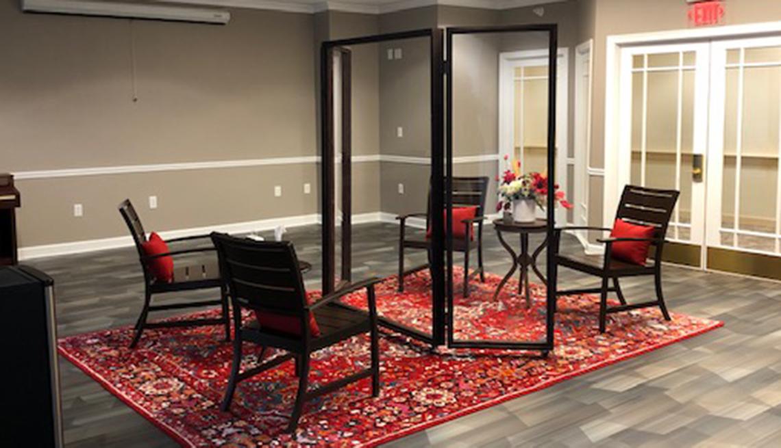 Una sala de estar familiar de un hogar de ancianos con sillas separadas por una mampara de vidrio.