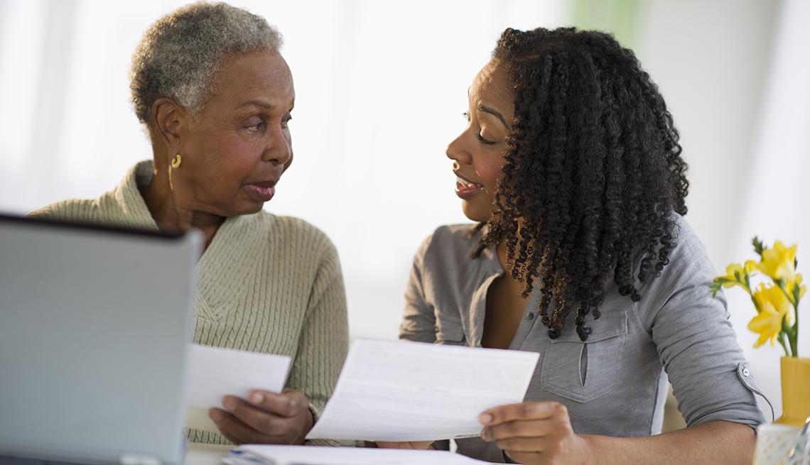 Mamá e hija adulta sentada en una mesa revisando el papeleo legal.