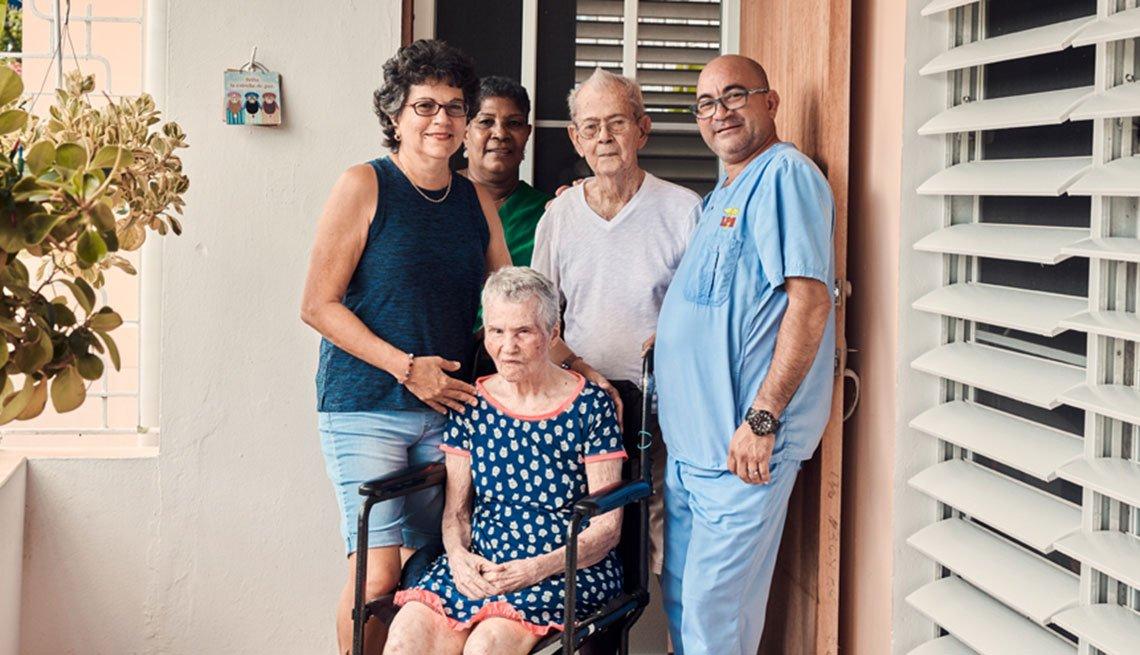 Mireya Pérez del Rio posa junto a sus padres en su hogar en Guaynabo, Puerto Rico, y con dos asistentes