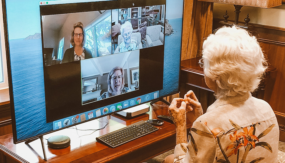 A female nursing home resident in a virtual chat suite visiting with family through the computer