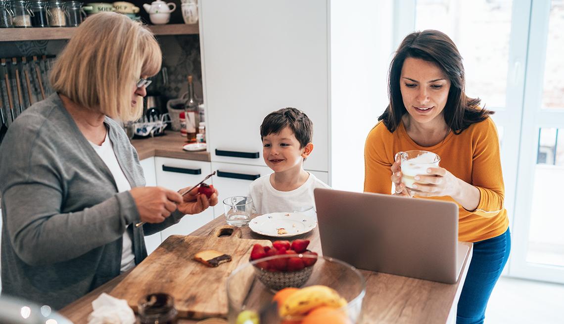 Una mujer trabaja en casa en una computadora portátil junto a su hijo y su madre.