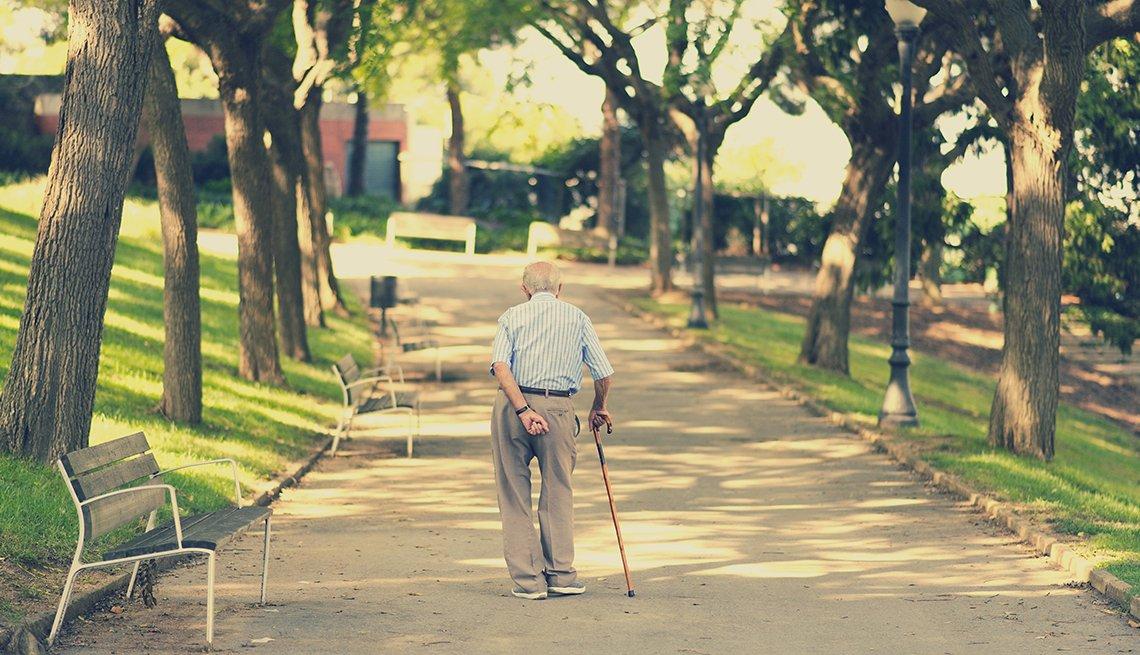 Un hombre con un bastón vagando solo por un parque.