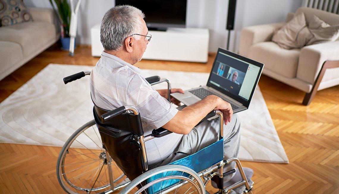 Hombre en su sala sentado en una silla de ruedas usando una computadora portátil para una cita de telesalud con su médico.