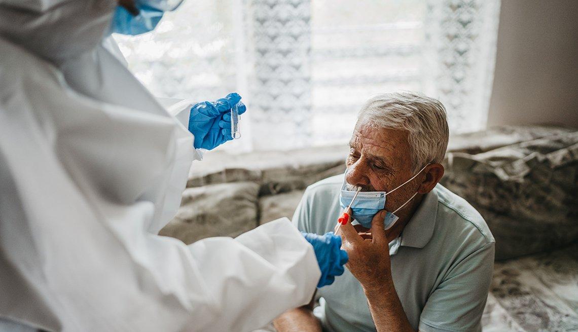 Un médico con traje de protección que toma la prueba de coronavirus con hisopo nasal de un residente de un hogar de ancianos masculino.