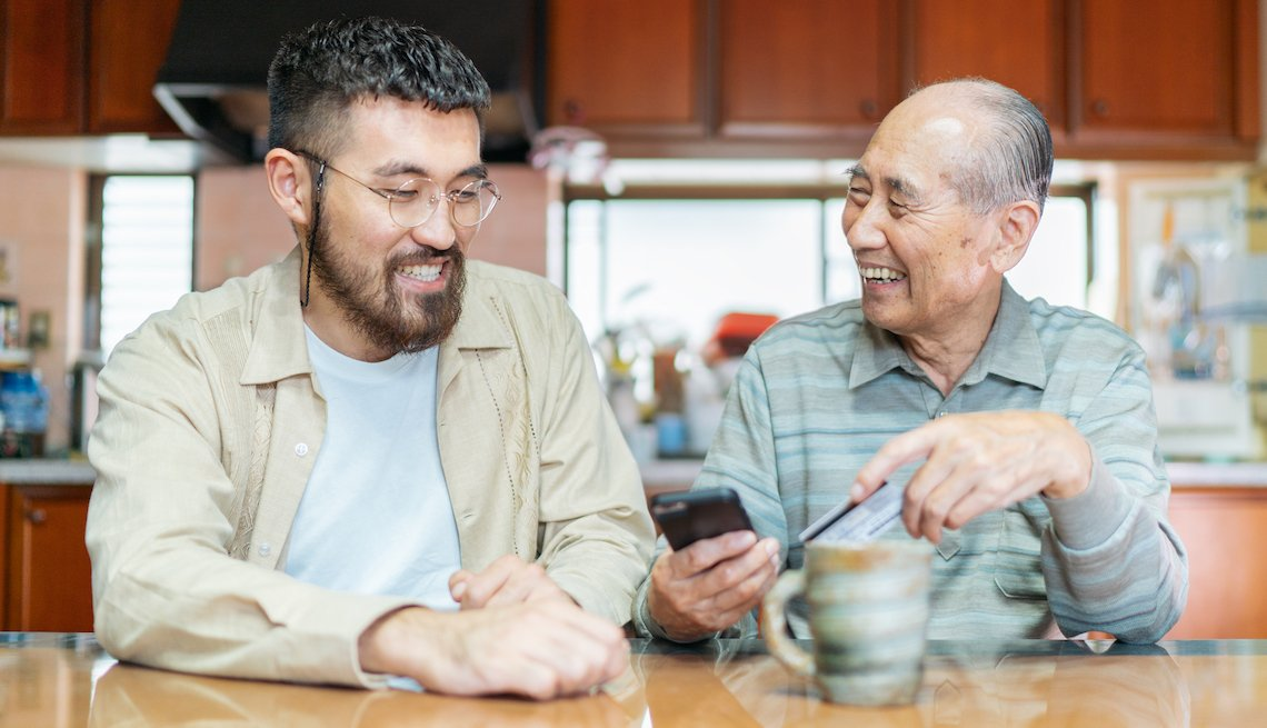 Asian American man helping his grandfather at home