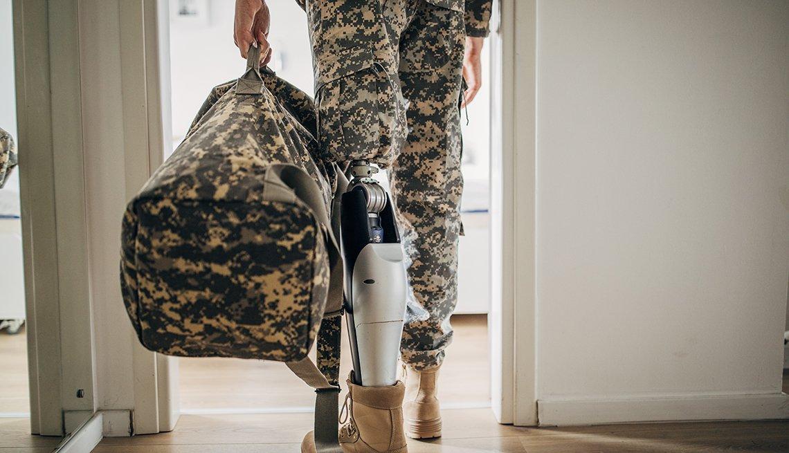 Un hombre con uniforme militar con una pierna amputada caminando por la puerta de una casa.