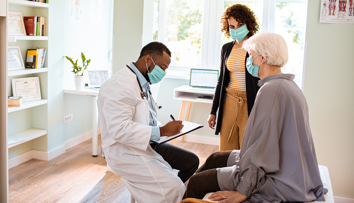A woman and her adult daughter talking with a doctor in his office. All are wearing face masks