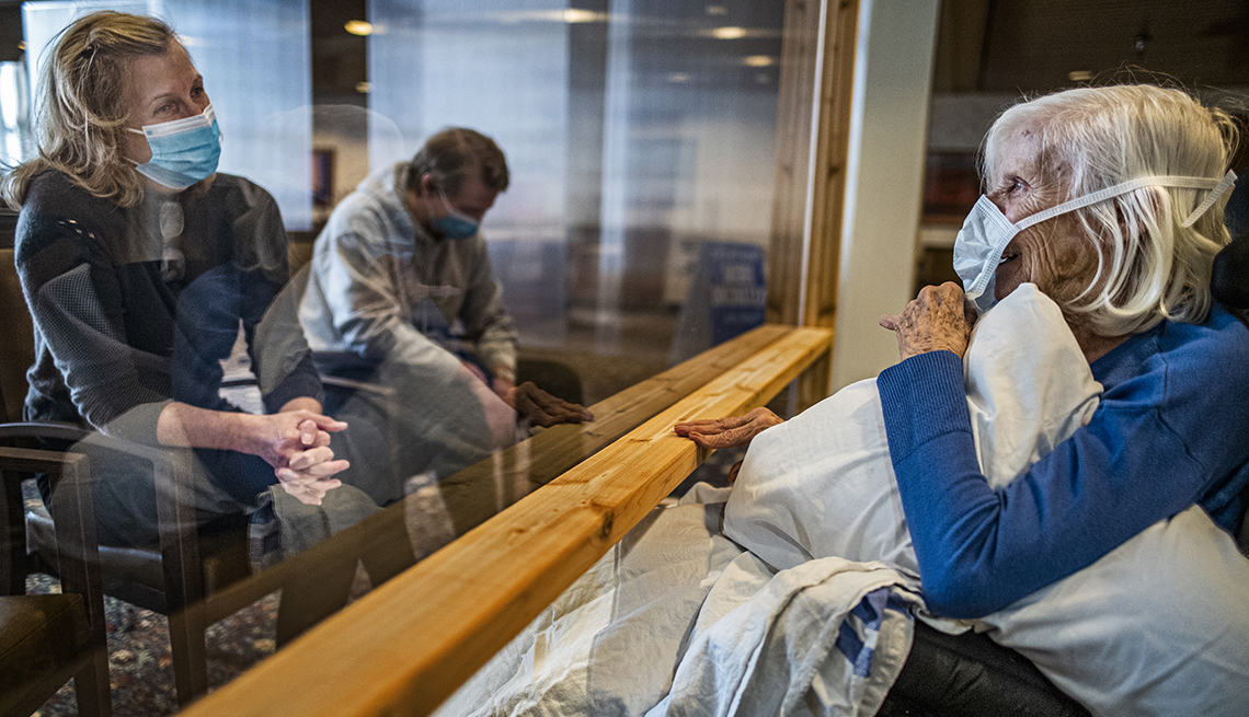 A female nursing home resident visits with her daughter and grandson through a glass partition