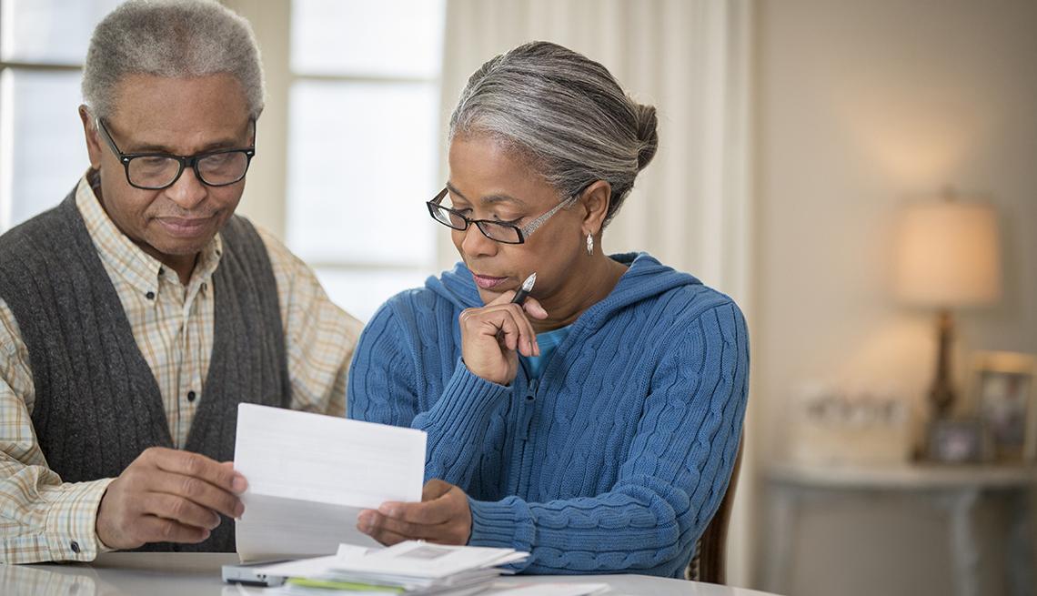 Una pareja mirando documentos de planificación de la jubilación.