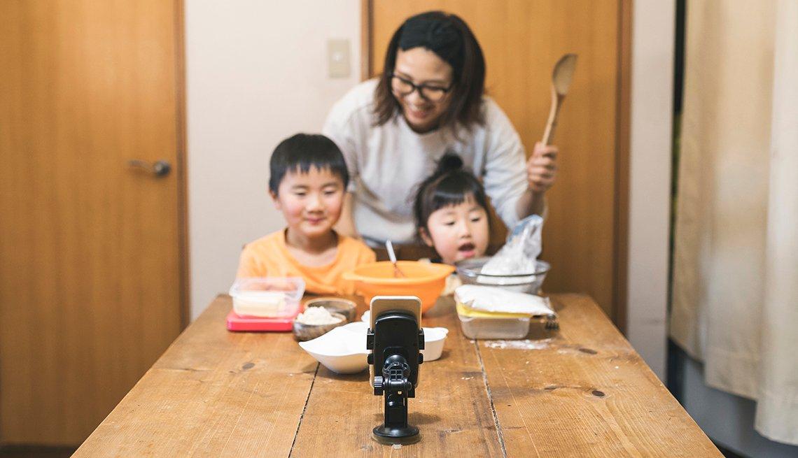 Una madre y sus dos hijos horneando galletas navideñas con su abuela mediante chat de video en un teléfono móvil.