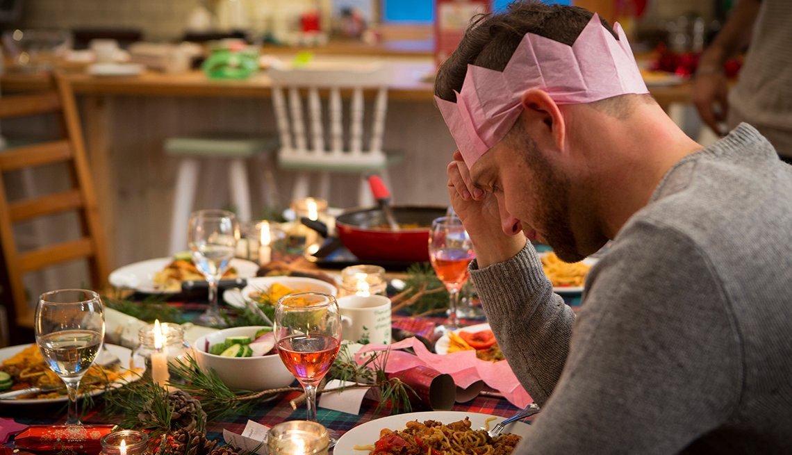 man sitting at a dinner table decorated for the holidays looking upset
