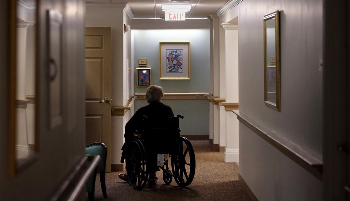 Un hombre sentado en una silla de ruedas en el pasillo de un hogar de ancianos.