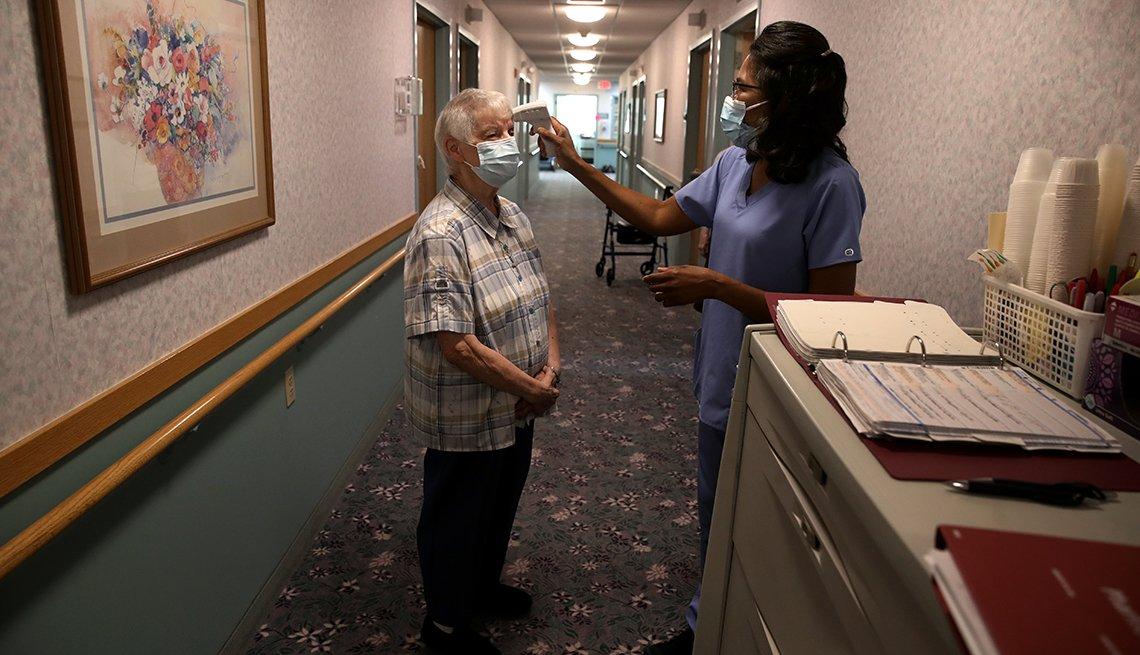 Una enfermera le toma la temperatura a una residente de un hogar de ancianos