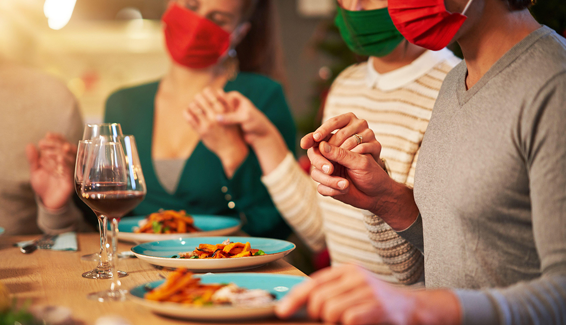 Family in face masks eating Thanksgiving dinner