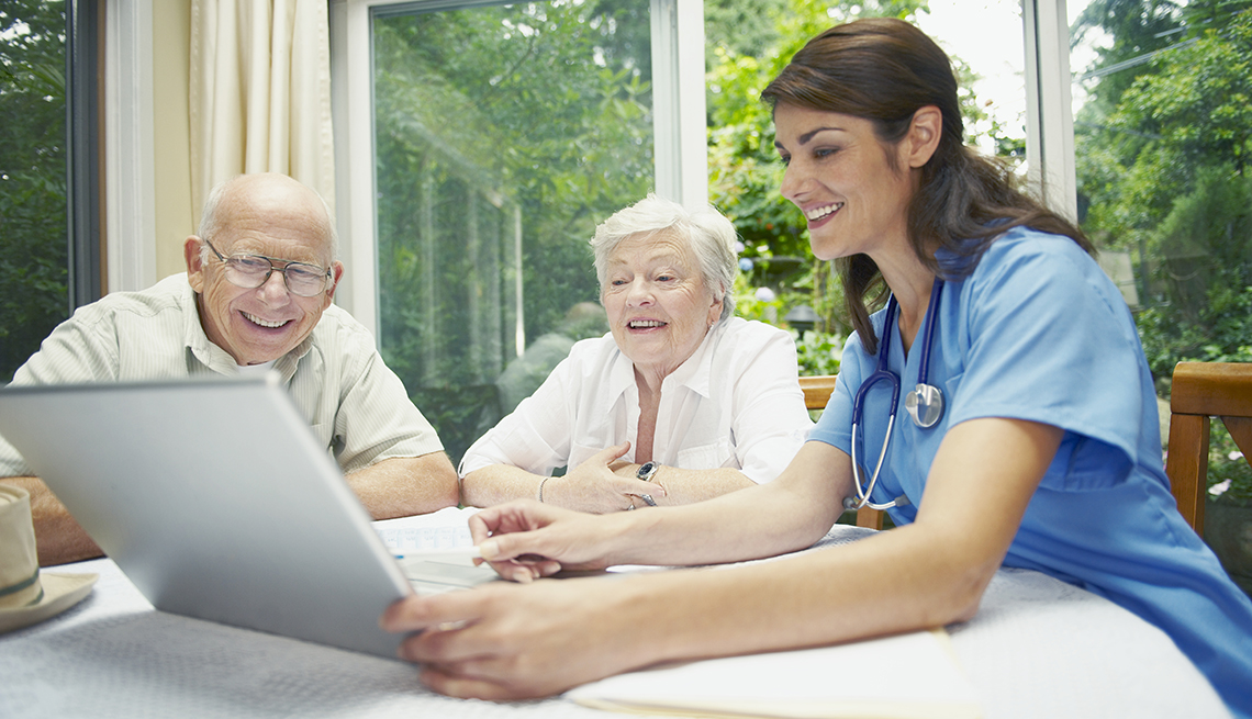Una enfermera le muestra un documento en una computadora a una pareja de ancianos