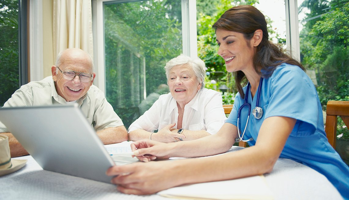 A nurse with a laptop consulting with a couple