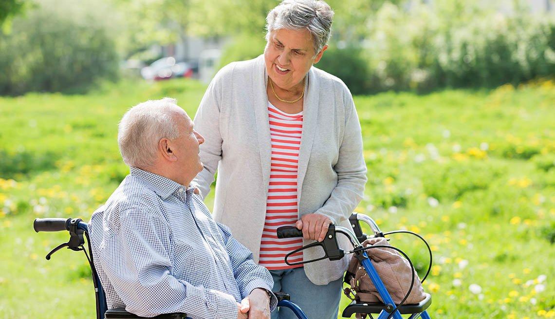Hombre en silla de ruedas junto a una mujer