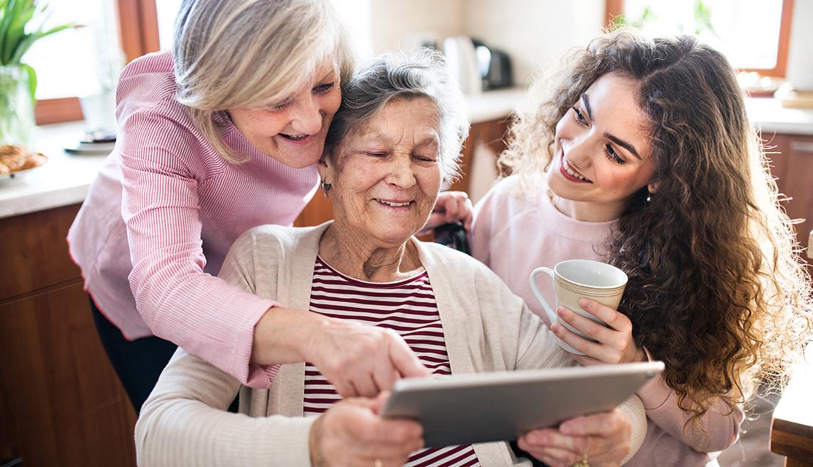 Tres generaciones de mujeres, abuela, hija y nieta usando una tableta