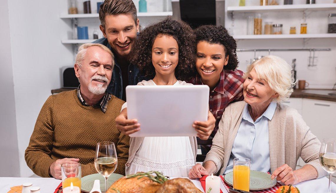 Una familia de cinco personas sosteniendo una tableta en la mesa de la cena conversando con miembros de la familia.