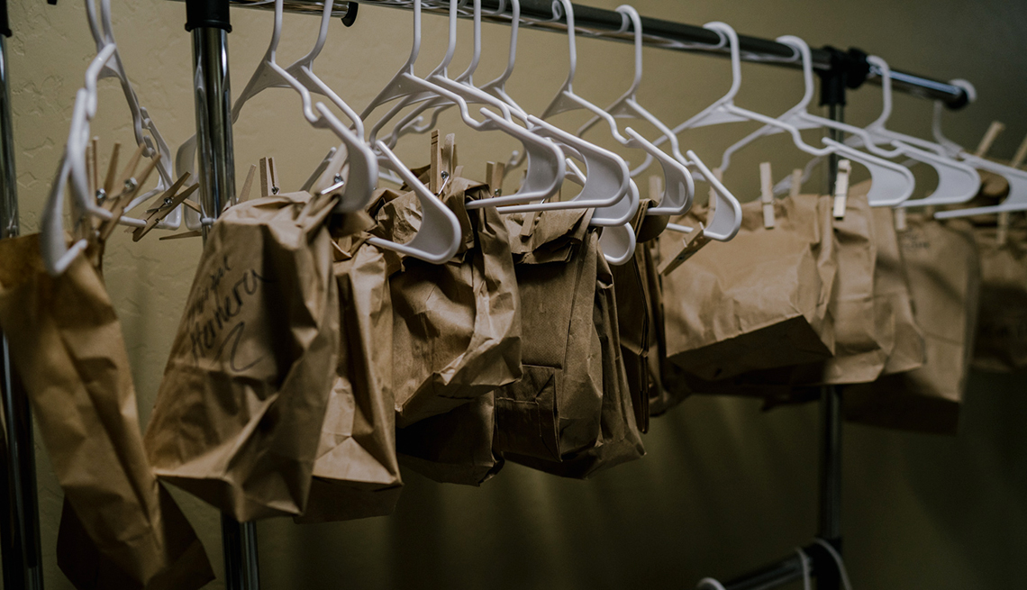 a closet full of hangers holding labeled paper bags one for each nurse face mask