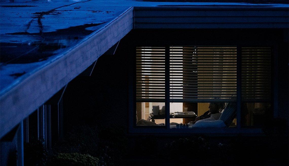 mirando por la ventana un residente de un hogar de ancianos.