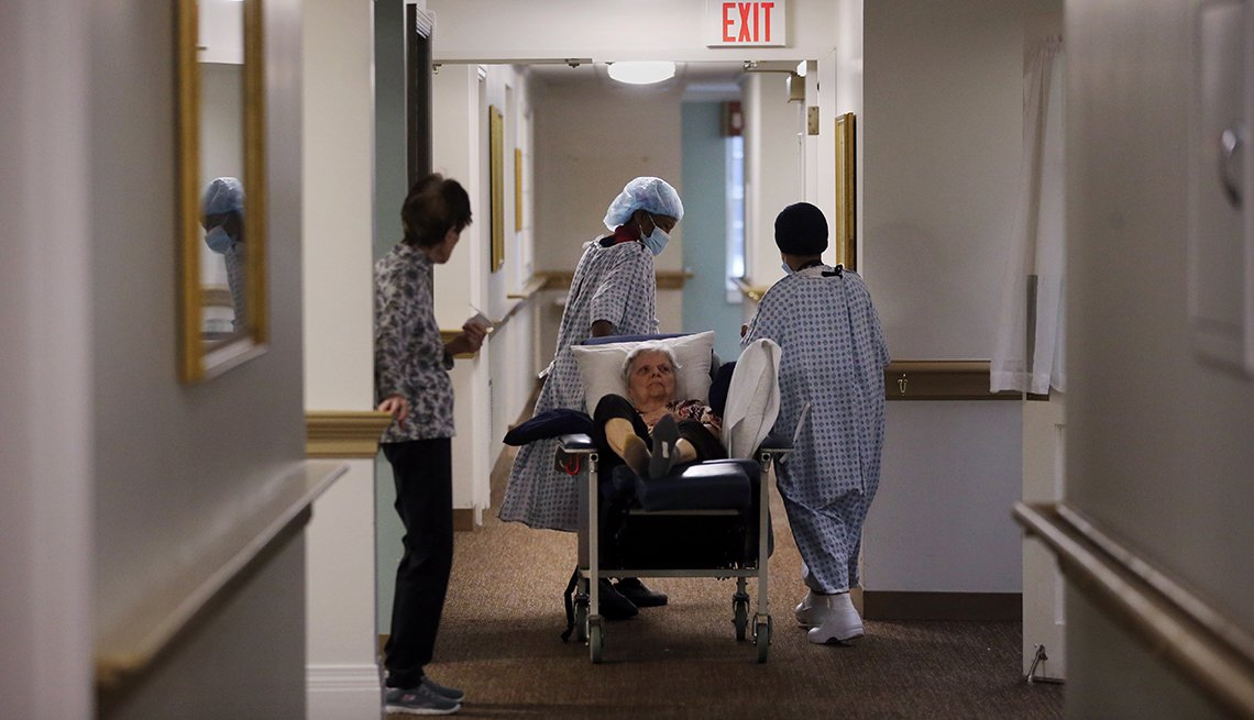 A nursing home resident being wheeled down the hall in a bed by workers wearing p p e