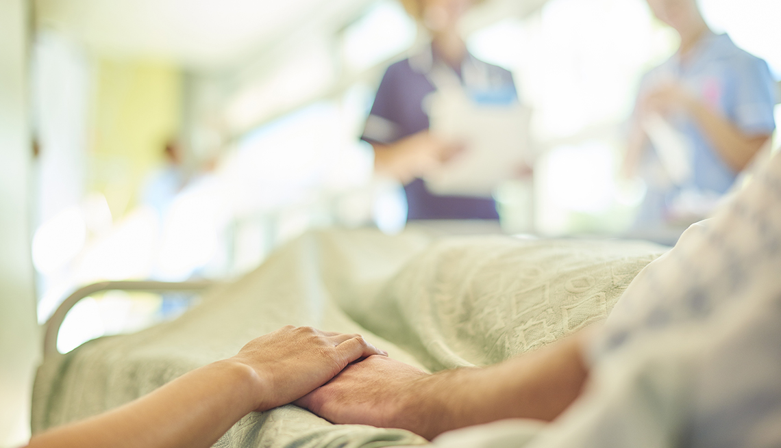 close up of a woman holding the hand of her dad who is in a hospital bed